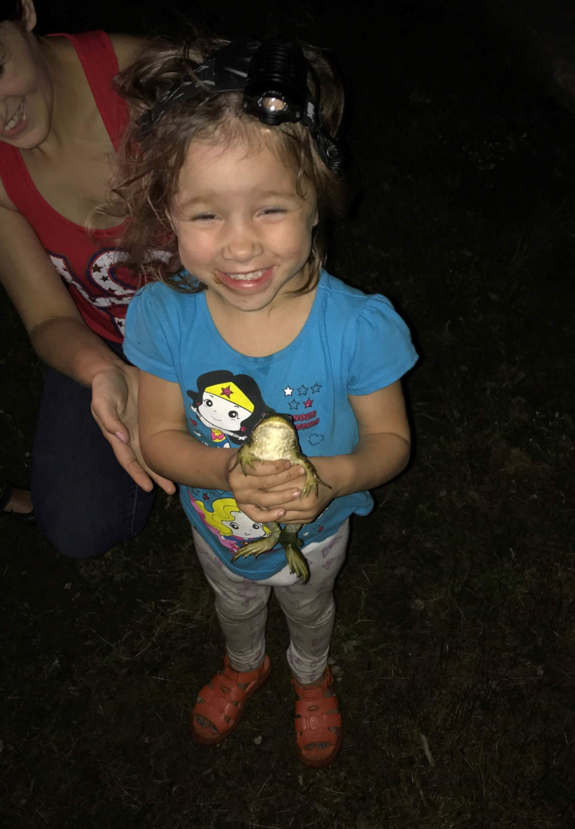 little girl with bullfrog outside herping at night